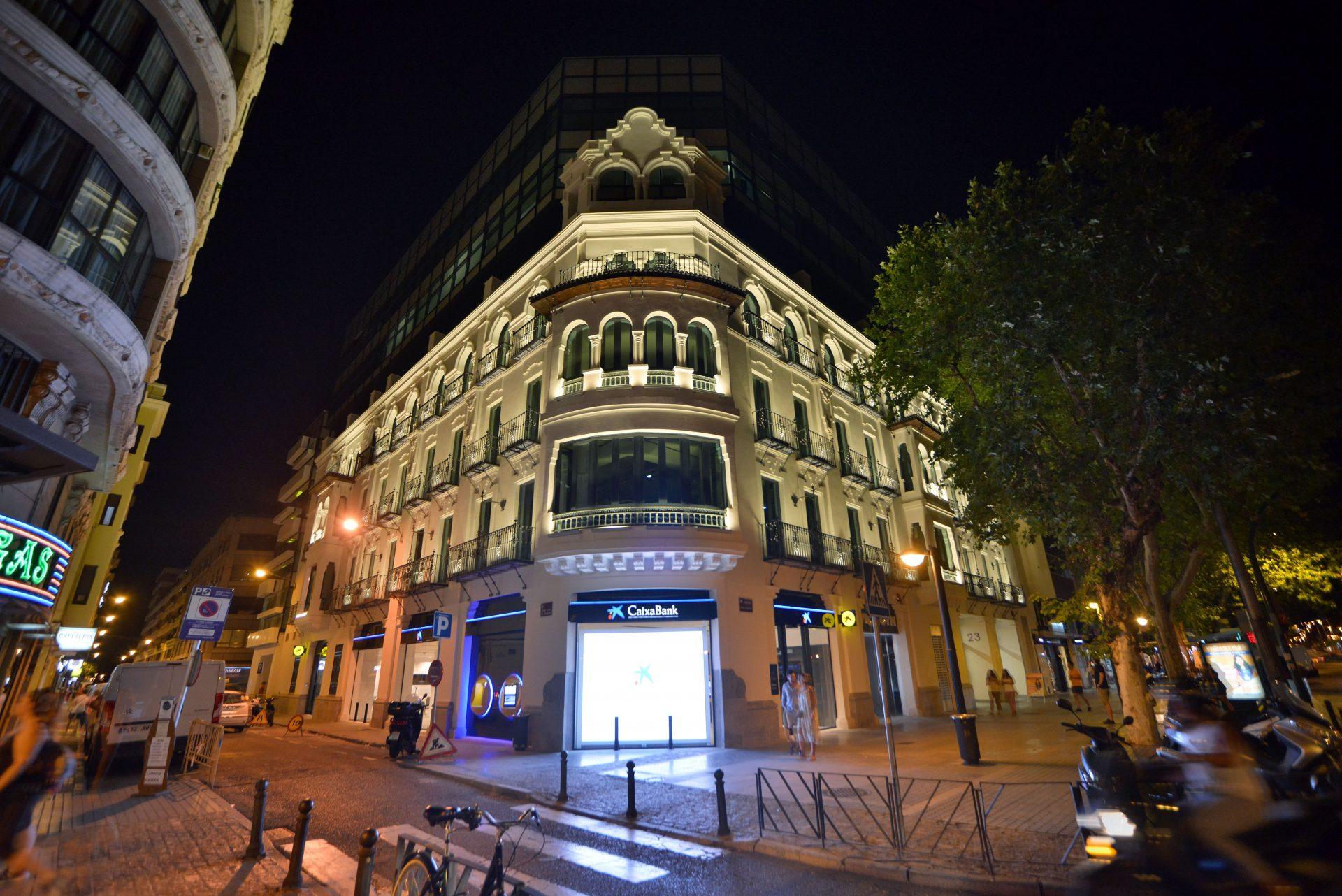 Fachada iluminada de noche de edificio singular para Caixabank en el centro de Córdoba