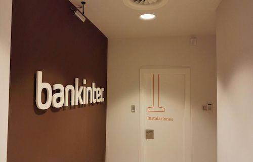 Letras blancas de Bankinter sobre fondo marrón en la pared